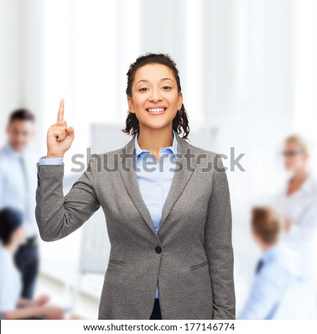 business and advertisement concept - attractive young woman with her finger up at office - stock photo