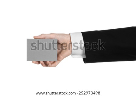 Business and advertising topic: Man in black suit holding a gray blank card in hand isolated on white background in studio
