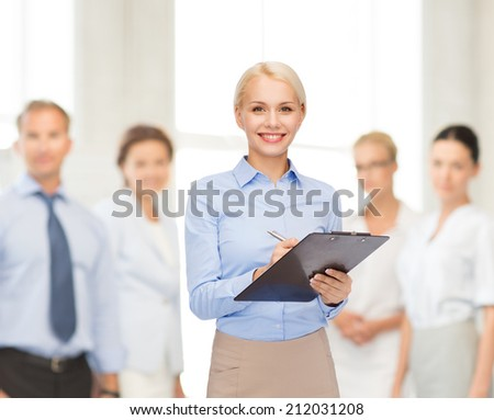 business and education concept - friendly young smiling businesswoman with clipboard and pen - stock photo