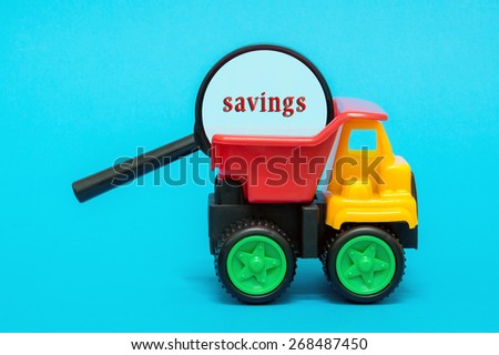Business and finance concept. Toy lorry carrying a magnifying glass looking for word SAVINGS on blue background - stock photo