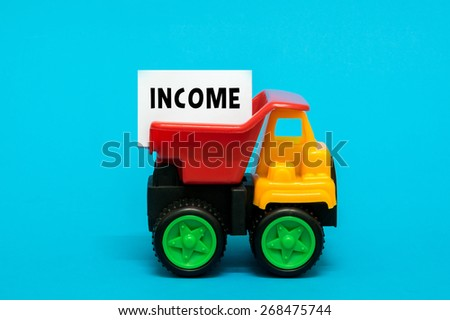 Business and finance concept. Toy lorry transporting an INCOME note on blue background. - stock photo