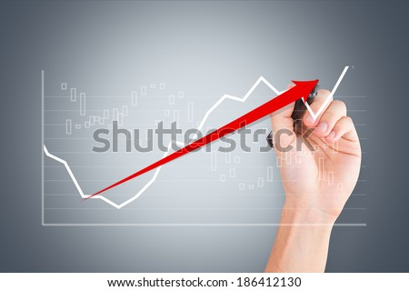 Business and finance concept, young male hand holding pen and drawing graph chart with red arrow on digital screen. - stock photo