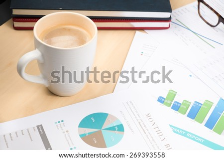 business and financial report with coffee.Graph,book,glasses,Document is mockup  - stock photo