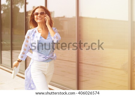 Business and freelance concepts. Close-up portrait of executive working with a mobile phone in the street with office buildings in the background. - stock photo