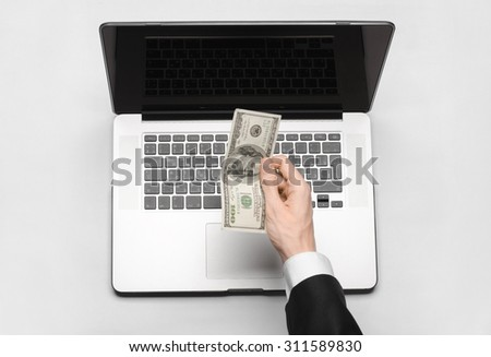 Business and freelance topic: hand in a black suit holding a banknote of 100 dollars on a laptop on a white table in the studio isolated top view - stock photo