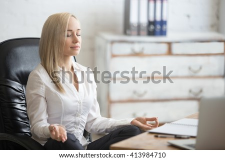 Business and healthy lifestyle concept. Portrait of young office woman sitting cross-legged in easy yoga pose at workplace. Smiling business lady meditating on her break time - stock photo