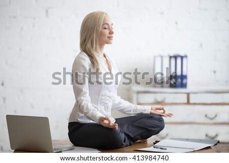 Business and healthy lifestyle concept. Portrait of young office woman sitting cross-legged in half lotus yoga pose at workplace. Smiling business lady meditating after finishing her work - stock photo