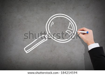 business and investigation concept - close up of businessman drawing magnifying glass on concrete wall - stock photo
