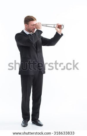 Business and money concept. Businessman using telescope isolated isolated on white background. Man in black business suit observing his competitors's strategies.