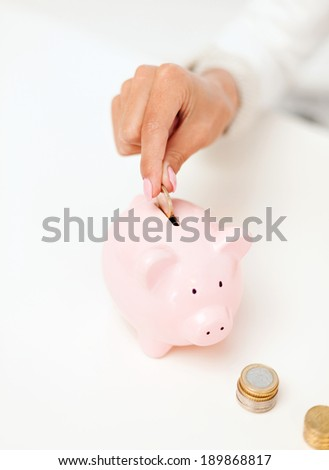 business and money saving concept - close up of female hand putting euro coins into piggy bank in office