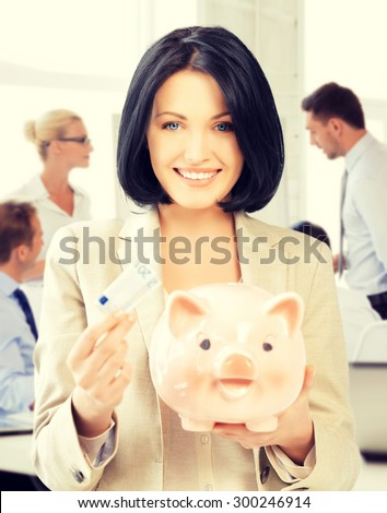 business and money saving concept - woman with piggy bank and cash money - stock photo