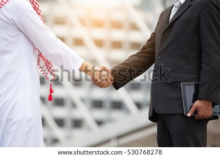 Business and Office concept - Arab and business man are shaking hand on cityscape background
