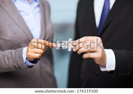 business and office concept - businessman and businesswoman holding puzzle pieces in office - stock photo