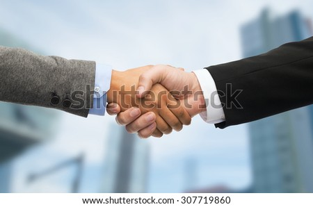 business and office concept - businessman and businesswoman shaking hands - stock photo
