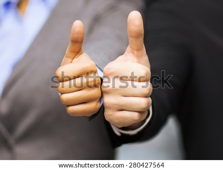 business and office concept - businessman and businesswoman showing thumbs up in office - stock photo
