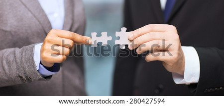 business and office concept - businessman and businesswoman trying to connect puzzle pieces in office - stock photo