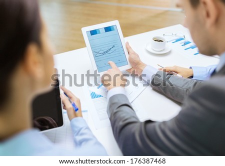 business and office concept - close up of business team with graph on tablet pc screen and coffee in office