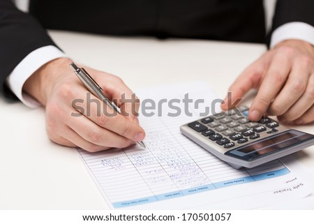business and office concept - close up of businessman with papers and calculator