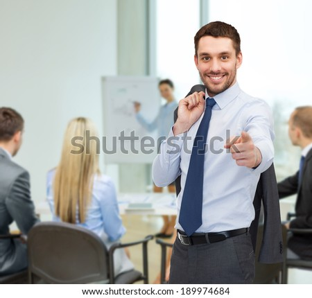 business and office concept - handsome buisnessman with jacket over shoulder pointing finger at you - stock photo