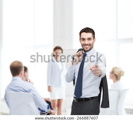 business and office concept - handsome buisnessman with jacket over shoulder pointing finger at you