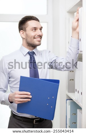 business and office concept - handsome businessman holding folder and picking another one at office - stock photo