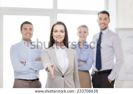 business and office concept - smiling beautiful businesswoman ready for handshake with team in office - stock photo