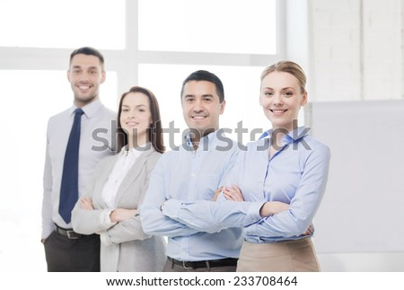 business and office concept - smiling beautiful businesswoman with crossed hands and team in office - stock photo
