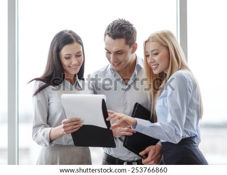 business and office concept - smiling business team looking at clipboard - stock photo