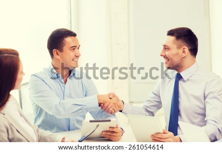 business and office concept - smiling business team with tablet pc computers in office shaking hands - stock photo