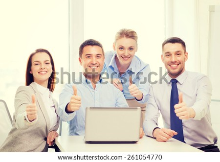 business and office concept - smiling business team working with laptop computer in office showing thumbs up - stock photo