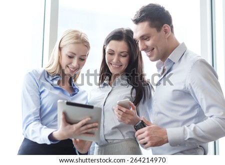 business and office concept - smiling business team working with tablet pcs and smartphones in office - stock photo