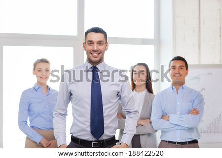 business and office concept - smiling handsome businessman with team in office