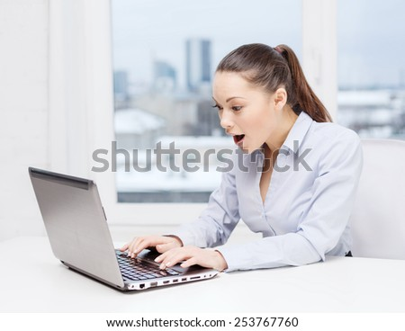 business and office concept - surprised businesswoman using her laptop computer - stock photo