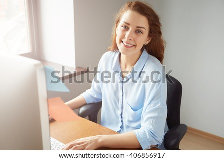 Business and office concept. Young woman entrepreneur looking and smiling at the camera during working day. Portrait of attractive successful female worker hand typing on the computer in the office.