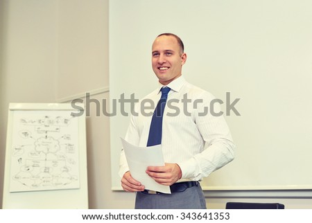 business and people concept - smiling businessman on presentation in office