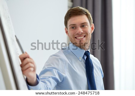business and people concept - smiling businessman pointing marker to flipboard on presentation in office - stock photo