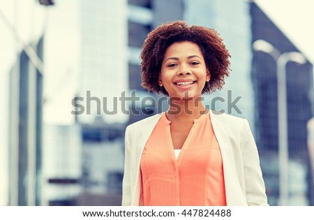 business and people concept - young smiling african american businesswoman in city - stock photo