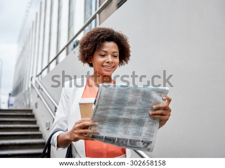 business and people concept - young smiling african american businesswoman with coffee cup going down stairs into city underpass - stock photo