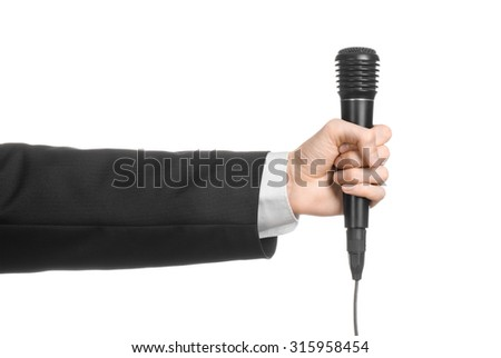 Business and speech topic: Man in black suit holding a black microphone isolated on white background in studio
