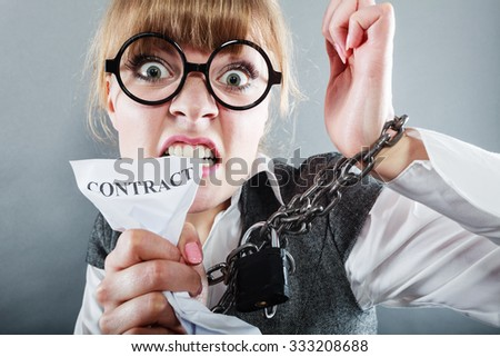 Business and stress concept. Furious businesswoman in glasses with chained hands holding contract grunge background unusual angle view - stock photo