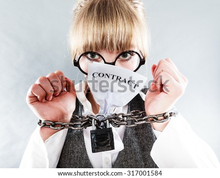 Business and stress concept. Terrified businesswoman in glasses with chained hands holding contract grunge background unusual angle view - stock photo