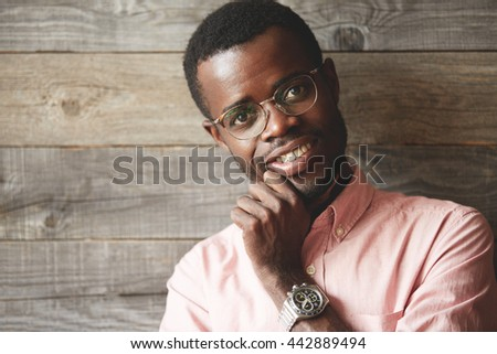Business and success concept. Close up shot of handsome dark-skinned entrepreneur in glasses and pink shirt, looking at the camera with happy confident smile showing white teeth, holding his chin - stock photo