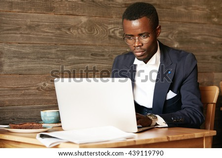 Business and success. Handsome successful African American man wearing formal suit, oval glasses and watches, using laptop computer for distant work, looking at the screen with serious face expression - stock photo