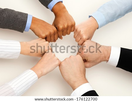 business and teamwork concept - closeup of businesspeople hands in fists in circle - stock photo