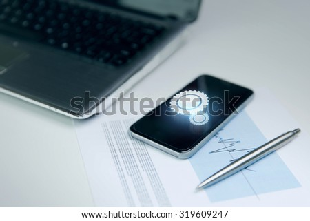 business and technology concept - close up of smartphone with cogwheel projection on screen, laptop computer and chart with pen on office table