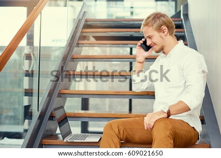 Business and technology. Handsome young man talking on smartphone in office.
