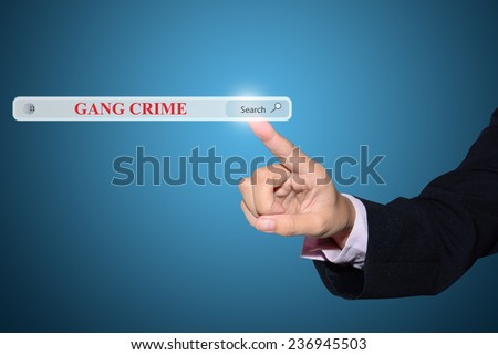 Business and technology, searching system and internet concept - male hand pressing Search GANG CRIME button.
