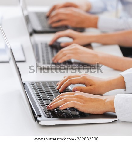business and telemarketing concept - group of people working with laptops in office - stock photo