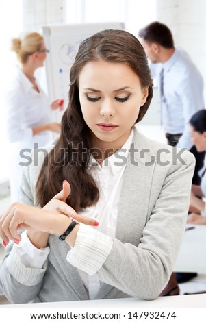 business and time management concept - businesswoman looking at alarm clock - stock photo