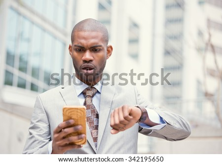Business and time management concept. Stressed business man looking at wrist watch, running late for meeting standing outside corporate office. Worried face expression. Human emotion  - stock photo